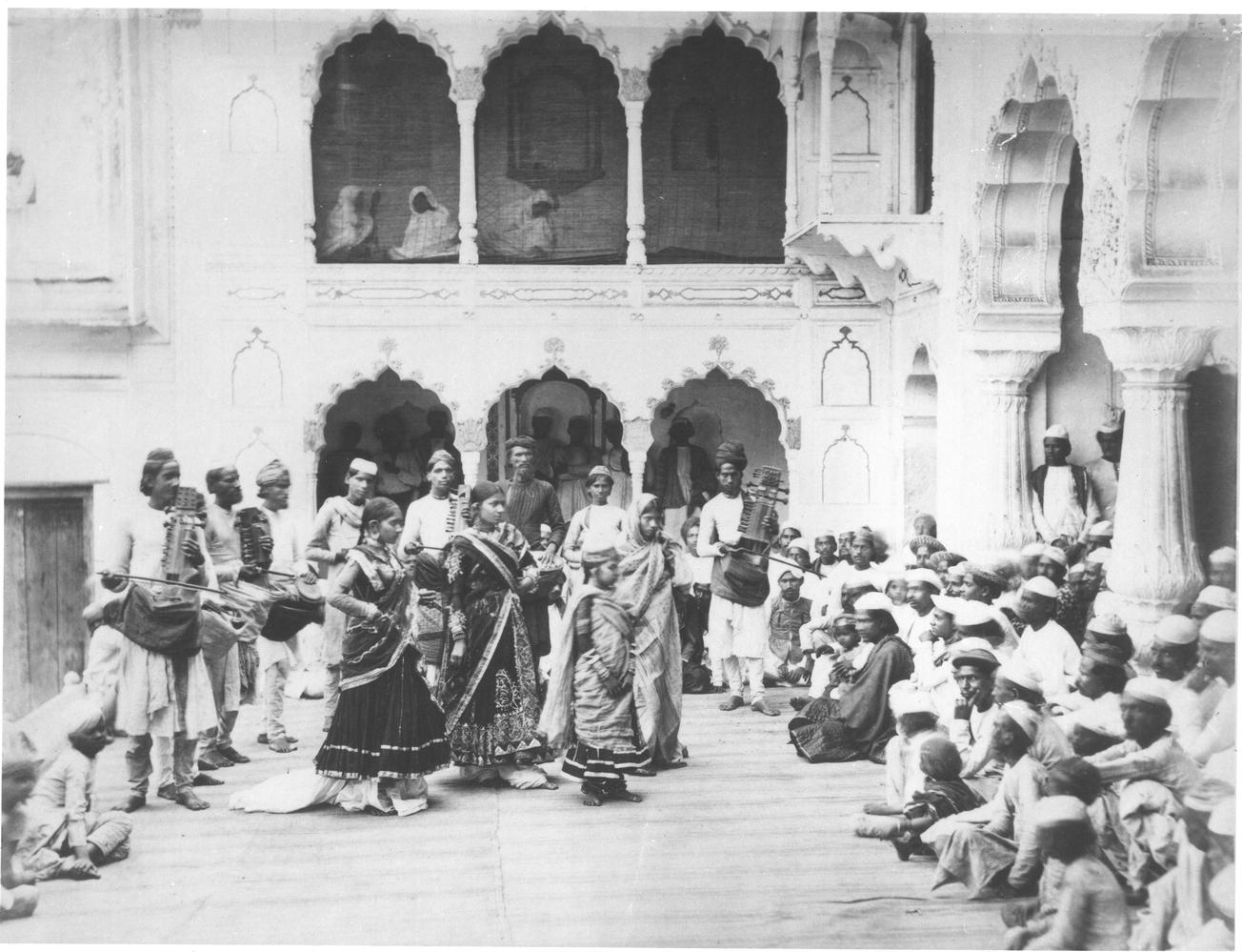 A photograph of several dancing girls and musicians performing to a crowd in a courtyard