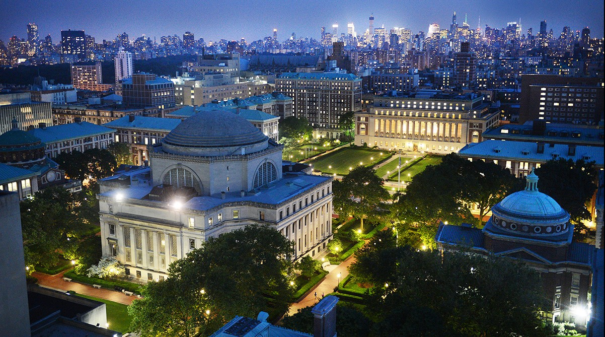Columbia University's Morningside campus stands at dusk against the glowing New York City skyline, majestic