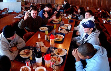 A group of seven students sit around a long table filled with food
