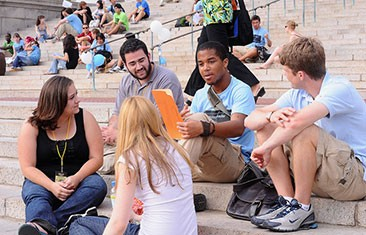 Five students sit on steps, talking