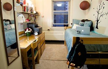 A dorm room with a desk on the left and a single bed on the right