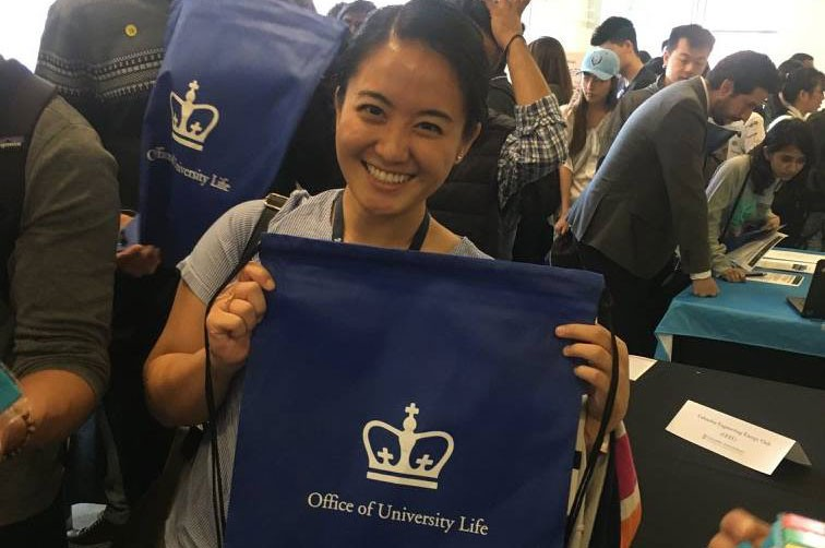 Student holding Office of University Life backpack