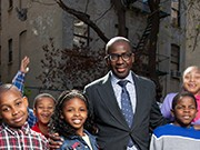 Olajide Williams, MD, director of the Wellness Center, stands in a playground with several children from the neighborhood (Credit: Columbia University)