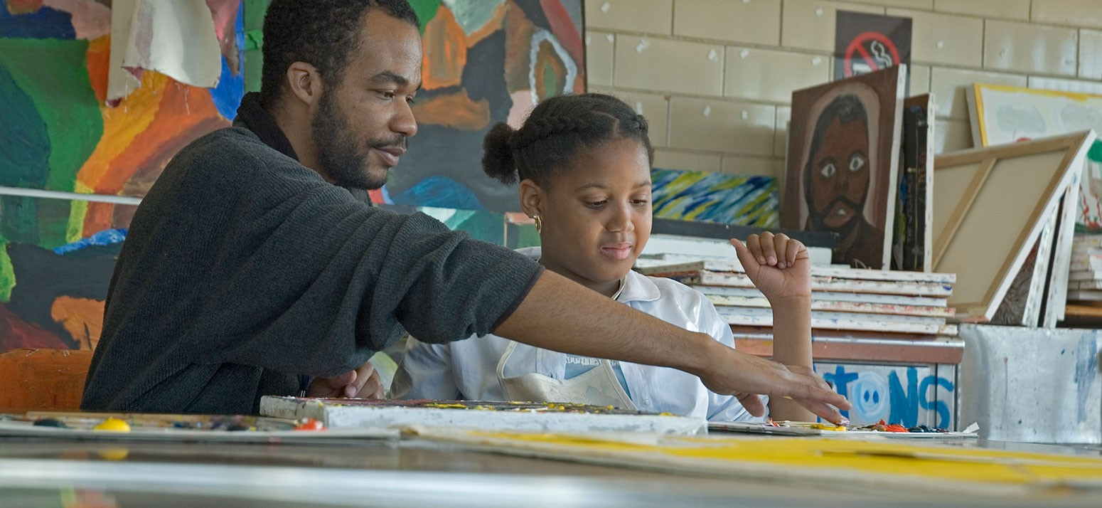 A man helps a young girl with an arts project