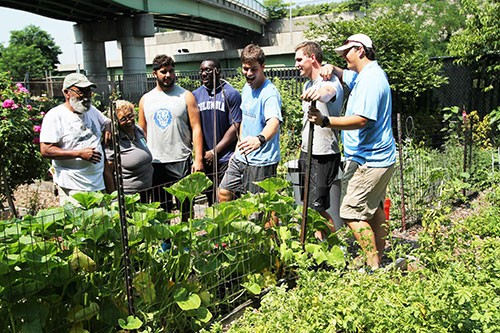 Five football players help a couple with their community garden