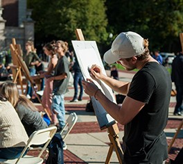A man stands at an easel drawing outside on the Plaza of Low Library, joined by more than a dozen others also drawing at easels.